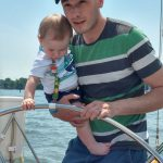 Man and baby steering boat