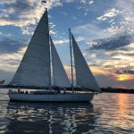 Schooner sailing on calm blue water with blue and orange sky