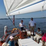 Women steering the schooner with pink hat on as captain stands by