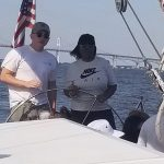 Women steering the boat with guidance from captain