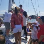 Group of guests learning how to raise the sails
