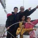 Family of five pointing to the left and steering the boat