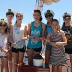 Girl Scout troop learning to sail and sporting captains hats