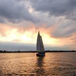 Schooner sailing into the sunset on dark waters