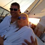 Couple smiling with blue water and sun sailing by