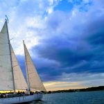 Sailing into a dramatic blue and yellow cloudy sunset