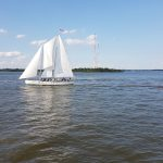 Schooner sailing with radio towers in back ground on calm waters