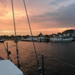 Boat coming into Annapolis Harbor with warm sunset all around