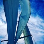 Looking up through the sails to a very blue sky turning the sails blue