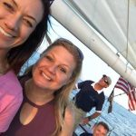 Two women enjoying their evening sail with captain in background