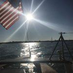 On board schooner with bright sun shining through American Flag