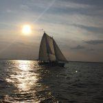 Schooner sailing with bright sunset above dark waters