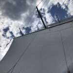 Looking straight up through sails and rigging at blue and white sky