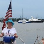 Women in blue hat steering the boat with Yachts in the background
