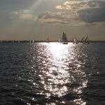 Colorful sailboats racing on Wednesday night at sunset