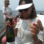Women holding up bottle of bubbly and glass on a sail