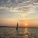 Sailboat framed by a bright yellow sunset on the Chesapeake