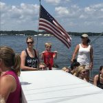 Young boy steering the boat with captains guidance