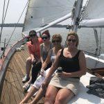 Four ladies all smiling and enjoying their sail