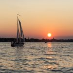 Schooner on the water with a big orange sun over blue waters