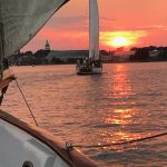 Schooners following each other into a bright orange and red sunset