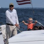 Captain helping a young boy with big smile steer the helm