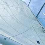 Looking straight up the mainsail into a bright blue sunny sky