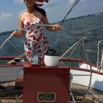Young girl in a sundress steering the boat with blue skies