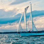 Sailing into the wind with guests aboard with blue skies and water