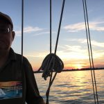 Guest sailing with sunset and water behind him