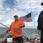 Guest steering the schooner with captain looking on