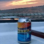 Seas the Bay IPA sitting on the deck with pretty sunset behind it