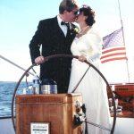 Bride and Groom steering schooner and kissing