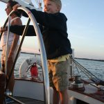 Young boy steering the schooner with captain supervision