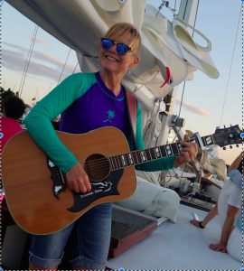 Sunset Sail with Entertainer Deanna Dove playing guitar
