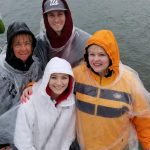 Four guests wearing clear ponchos and sailing in the rain