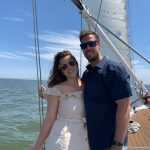 Smiling couple on deck posing in front of sail and blue water
