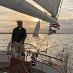 Captain steering helm with second schooner following at sunset