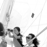Black and white photo of a women and child raising the sails
