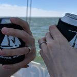 Two hands showing just married wedding bands toasting with cans