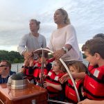 Five small children learning to steer the helm at one time