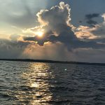 Sun peaking through clouds and reflecting on the dark water