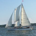 Schooner sailing with guests in blue waters with a blue sky above