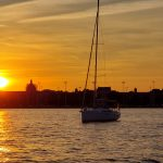 Sail boat with sails down and sunset behind it on the water