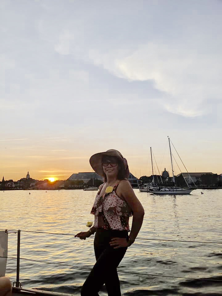 Women with summer hat posing in front of sunset on the water