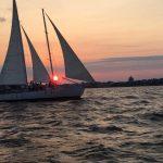 Schooner sailing with sun peaking through sails at sunset