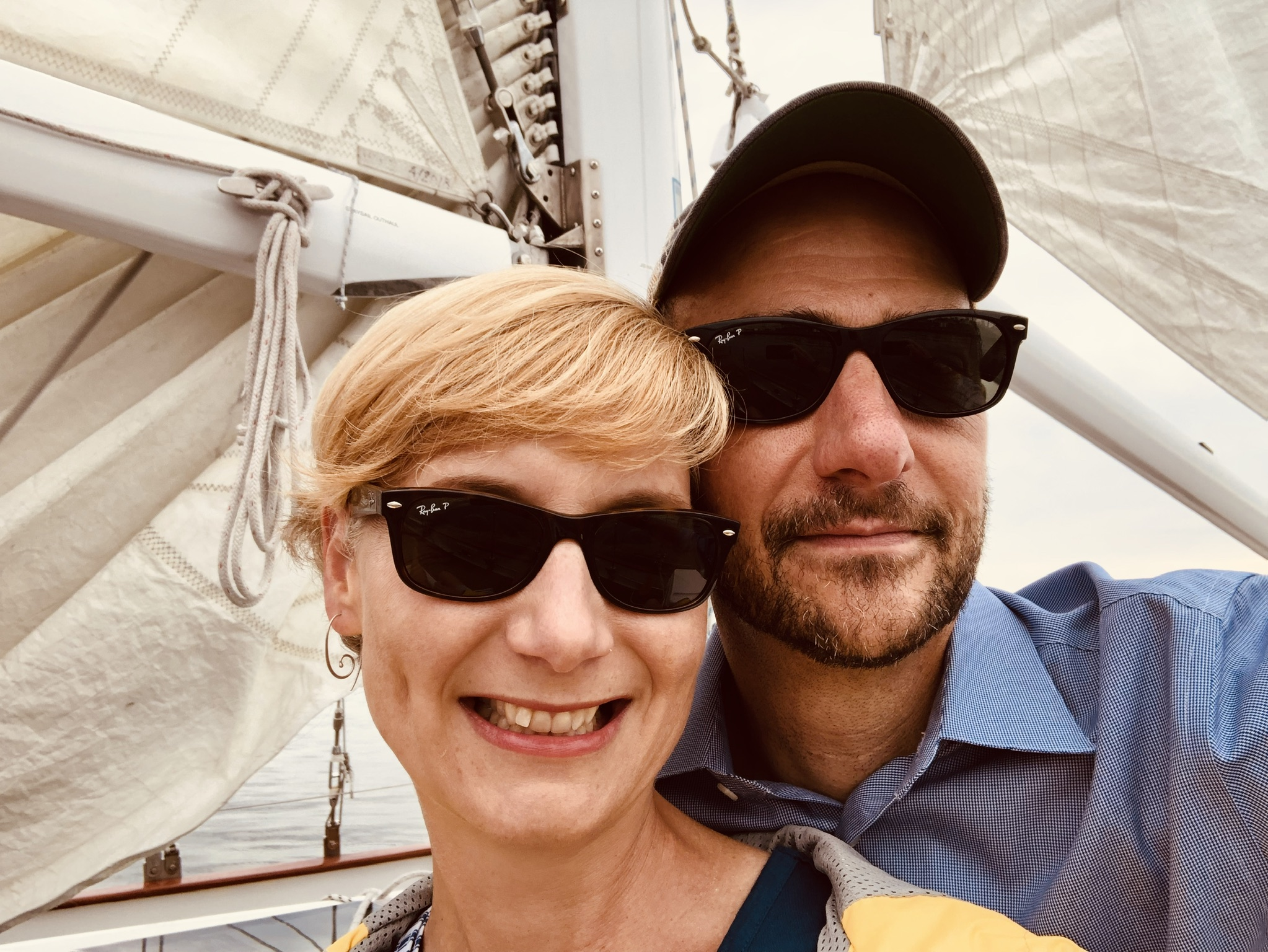 Man and Women with sunglasses enjoying a cruise on the schooner
