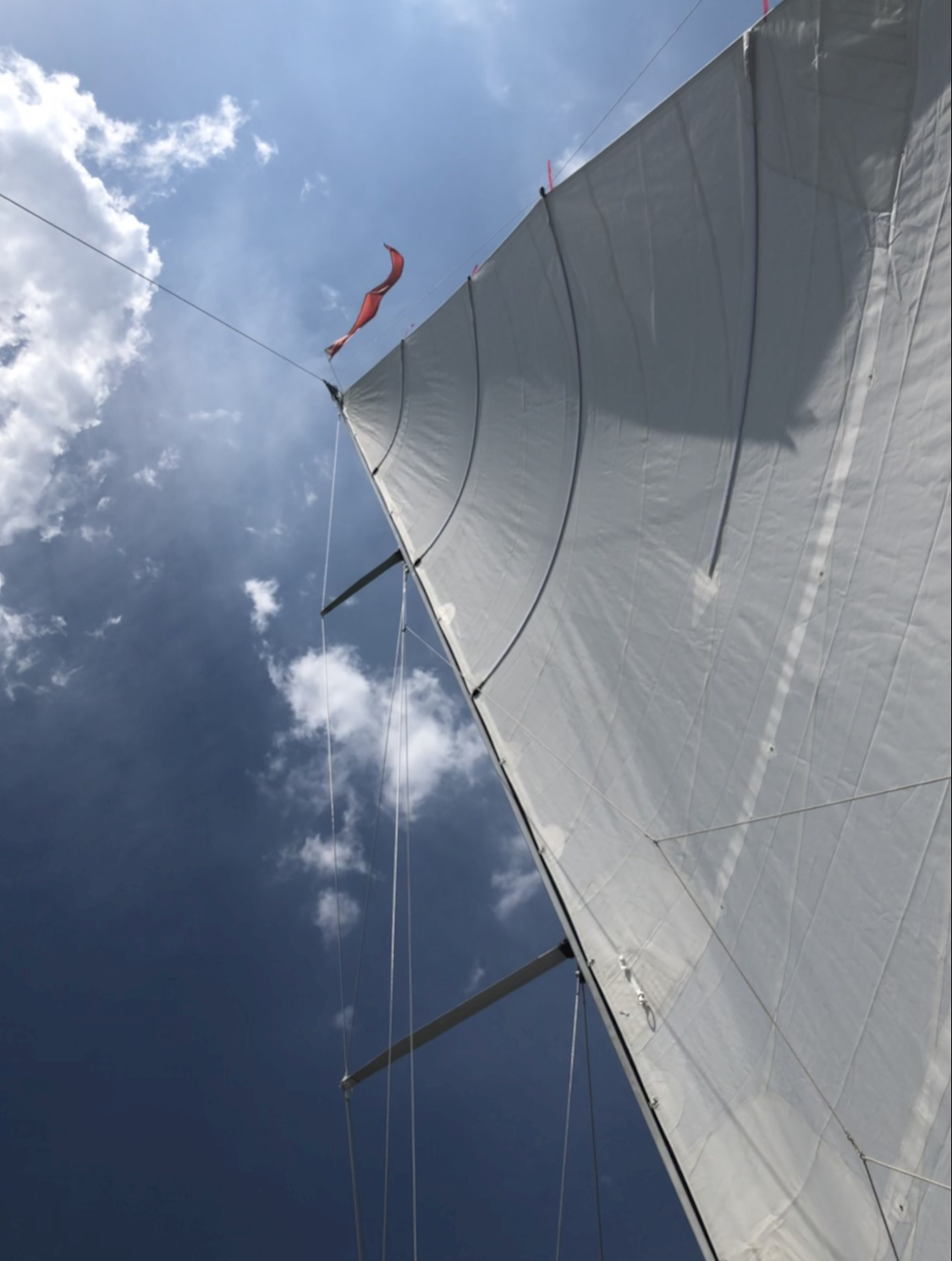 Looking up at the Mainsail to blue skies with puffy white clouds