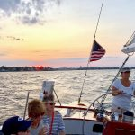 Schooner being captained at sunset with American Flag flying