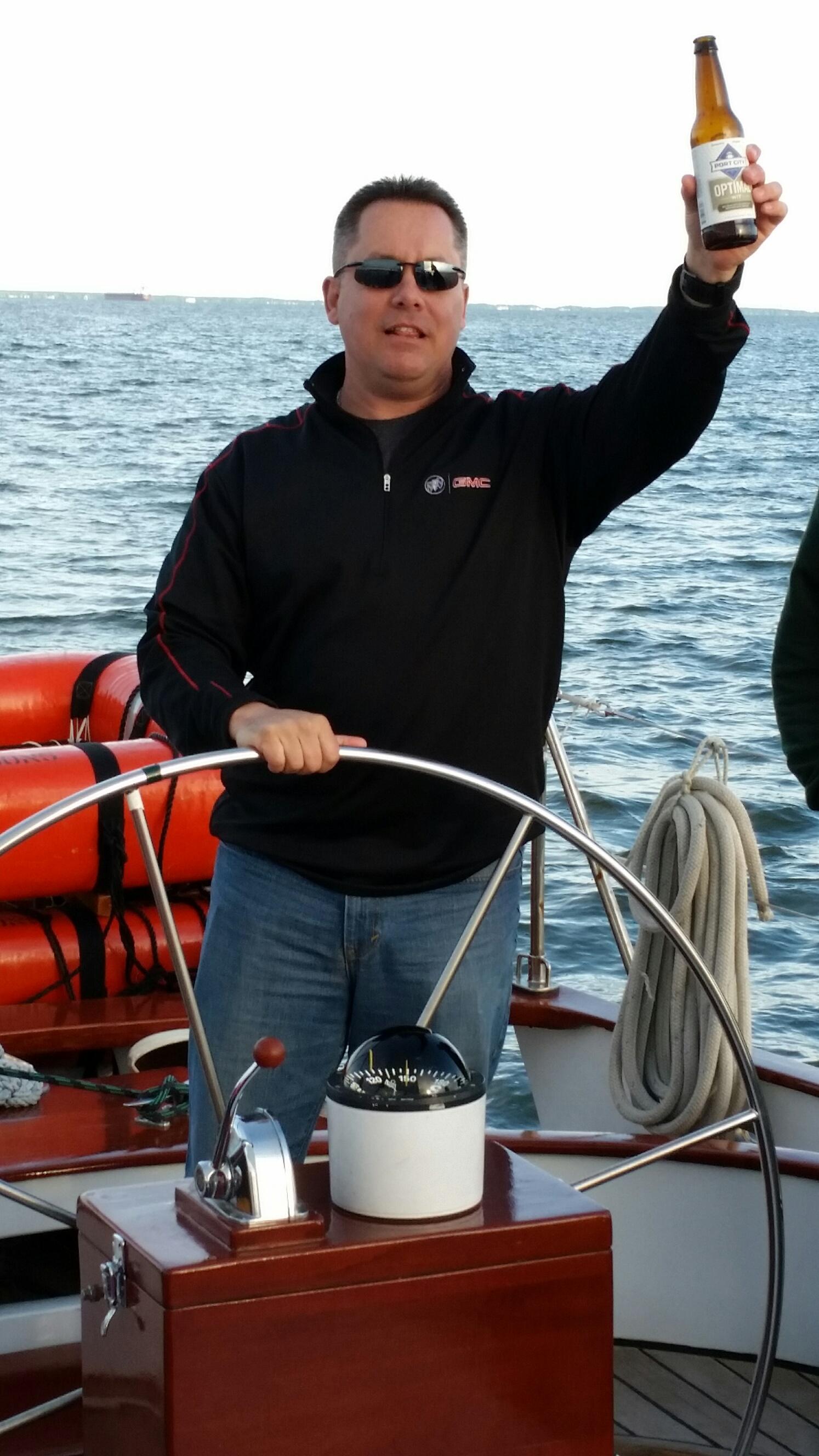 Guest steering schooner and cheering with a beer bottle